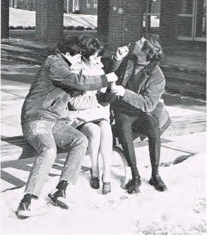 Three students sitting on a curb talking with each other.