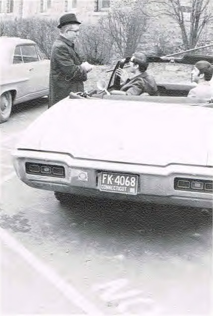 Students in a convertible talking to a professor