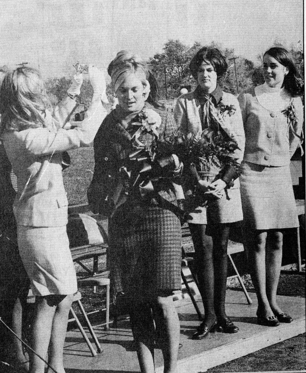 Girl holding a bouquet with her friends around her.