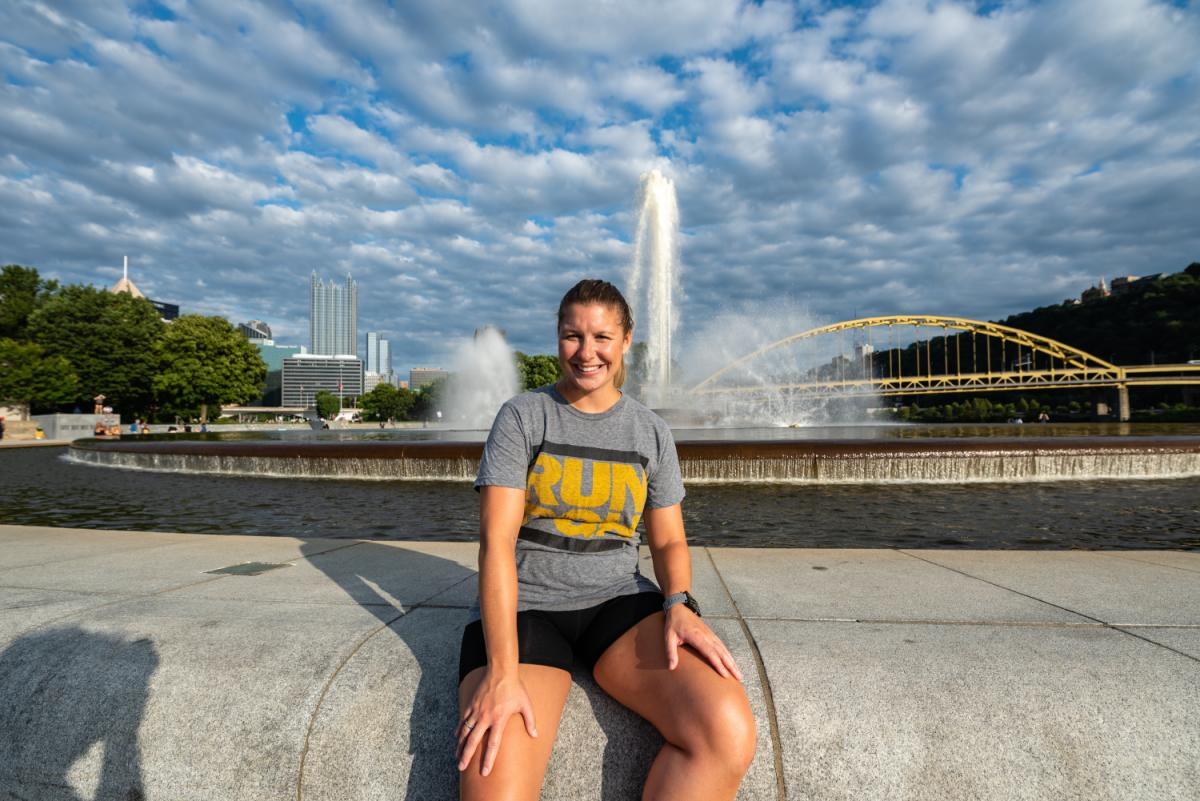 Amanda Hardt '13 sits with the Pittsburg skyline behind her