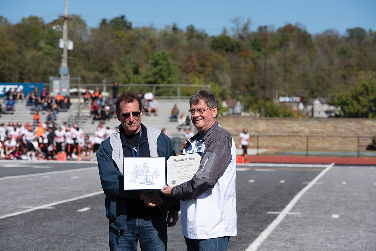 Jon Wendell '69.5 accepts and award from President Ruud on the football field