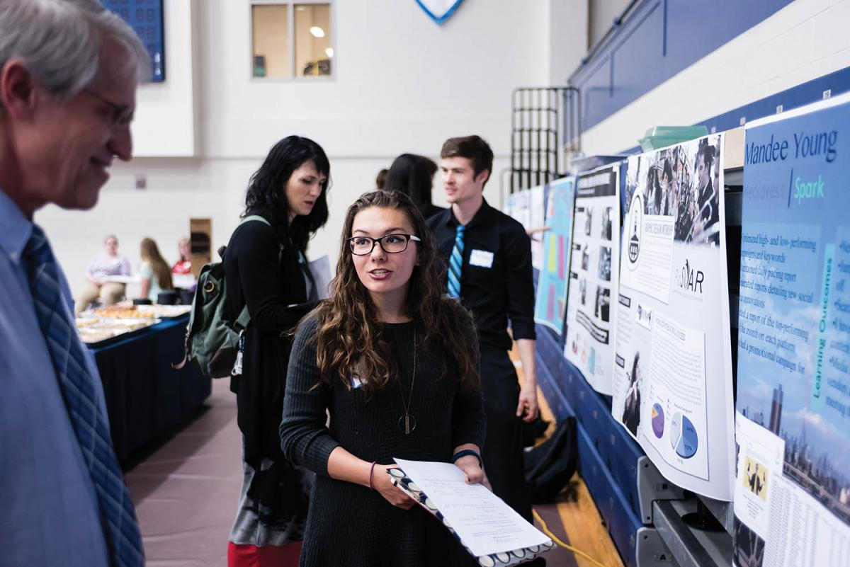 Mandee Young '18 discusses her internship with Mediavest | Spark with Dr. Bob Van Camp during the poster session of All Scholars Day.