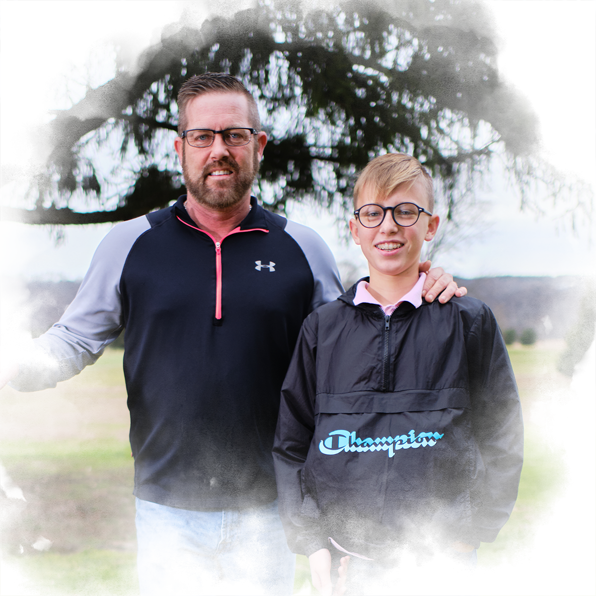 Shawn Shuster '98 stands holding a golf club with his son