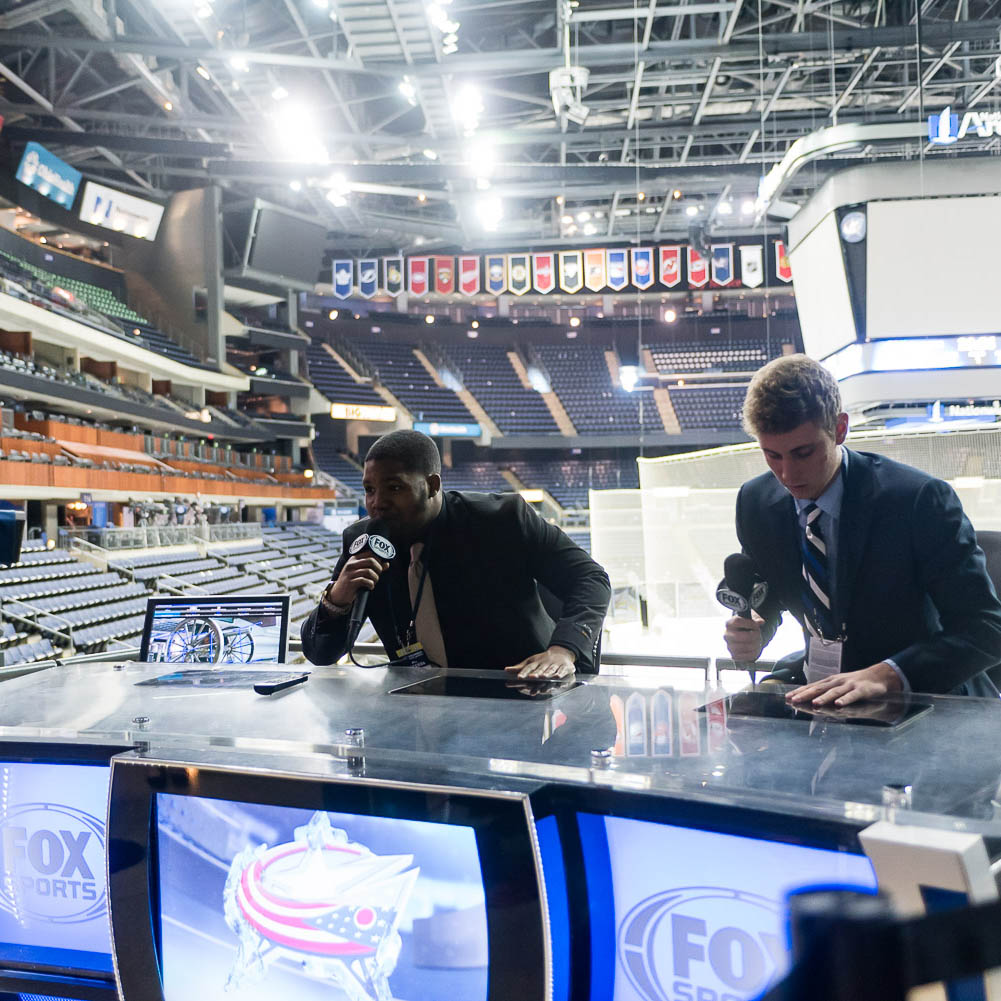 Stepping behind the curtain during their job shadow of the Columbus Blue Jackets, two students sit at a news table