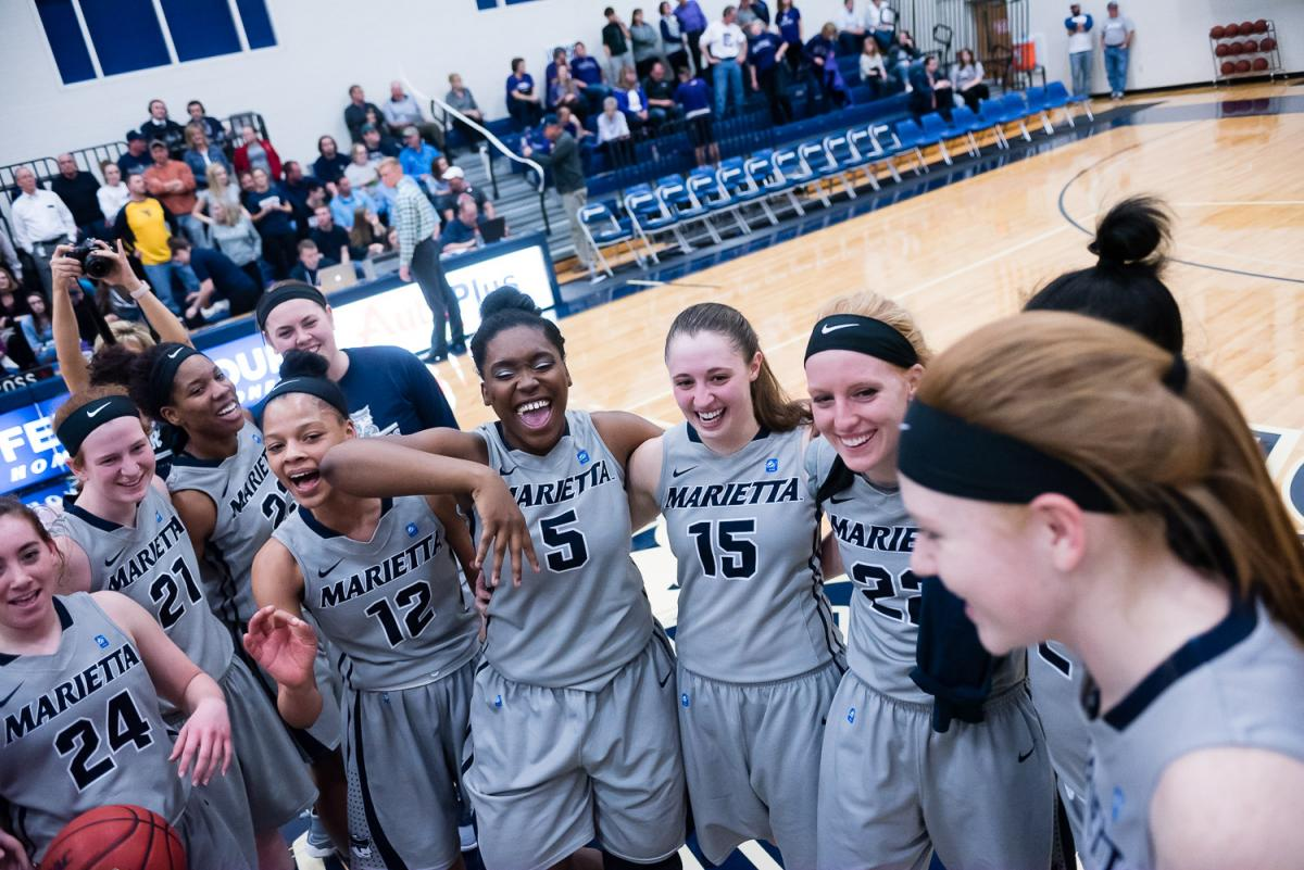 Marietta College Womens Basketball celebrating in a circle