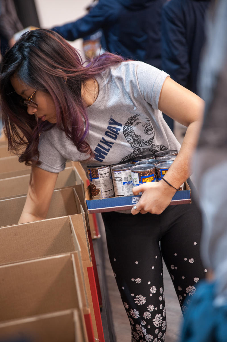A Marietta College student fills boxes with canned goods for the 2019 Day of Service