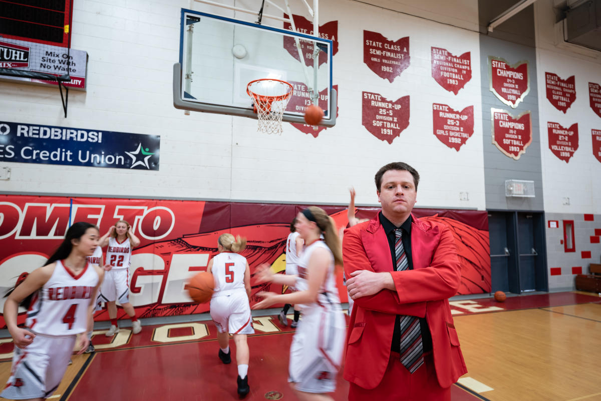 Tyler Bates '13 poses for a portrait as his basketball team runs drills behind him
