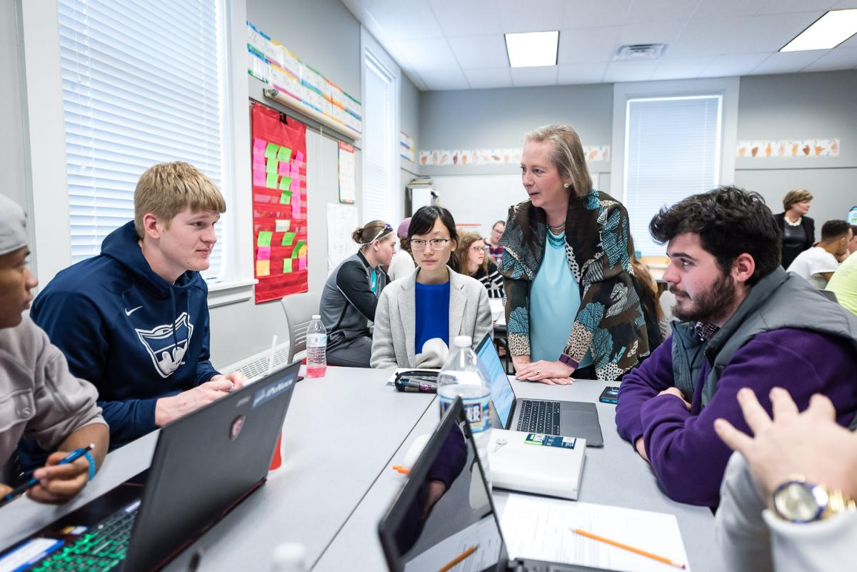 Dottie Herb of Marietta College talks with a table of students in the classroom