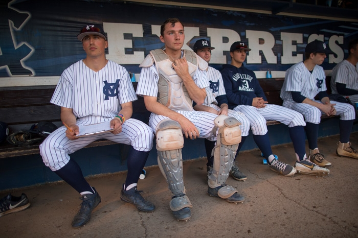 Players sit on the bench between innings