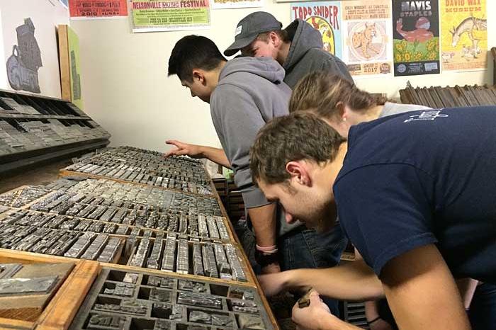 Students look for metal stamps at justAjar in downtown Marietta