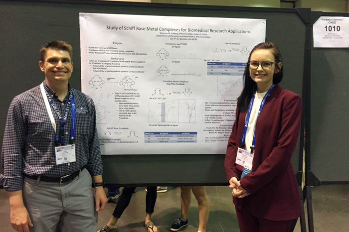 Dr. Jim Jeitler and Shannon Patberg standing in front of a research poster