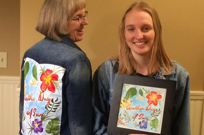 Two women - one facing and the other with her back - showing off artwork on jean jacket