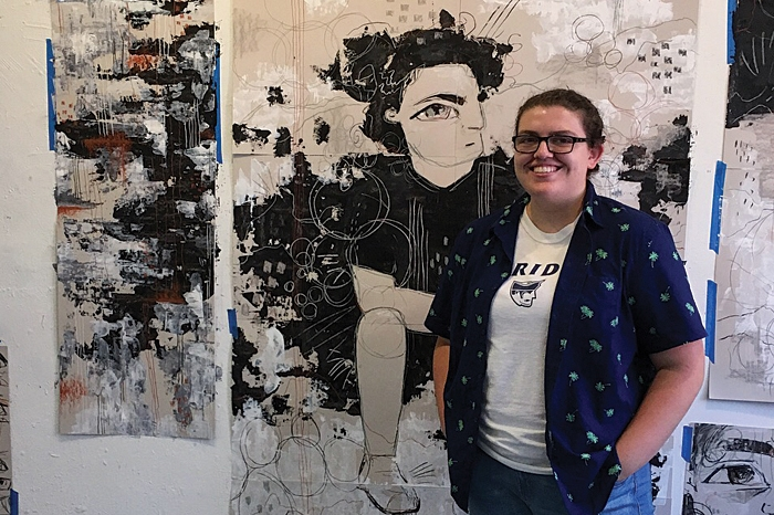 Hailey Bennett standing by her artwork in NYC