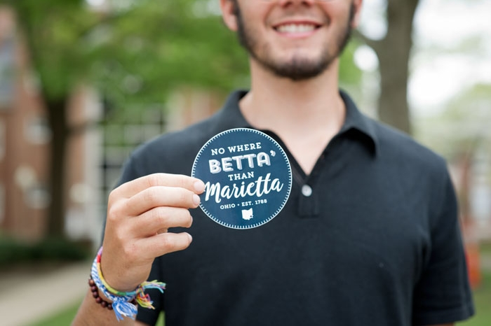 Male student holding sticker