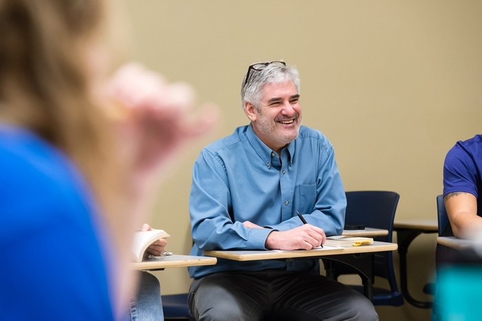 professor tim catalano sitting in a classroom