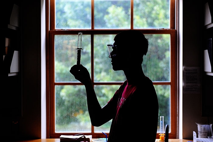 Male student standing in front of window while holding a chemistry beaker