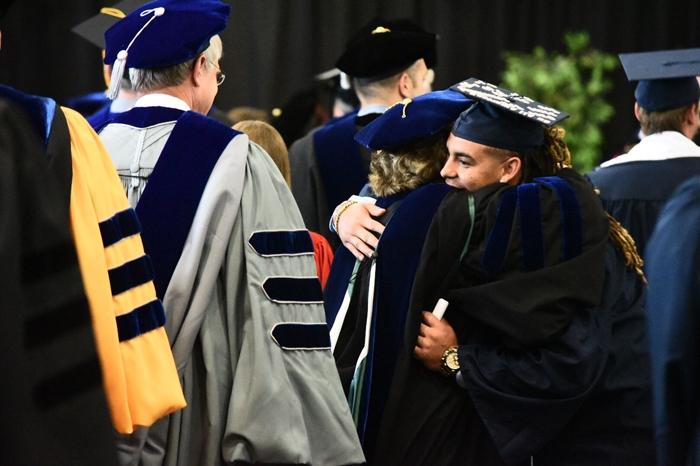 Senior Roger Walker hugging a faculty member