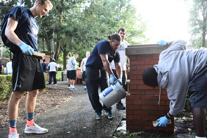 football players scrubbing the Fourth Street gateway