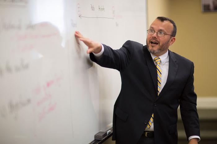 Gama Perruci teaching at a white board