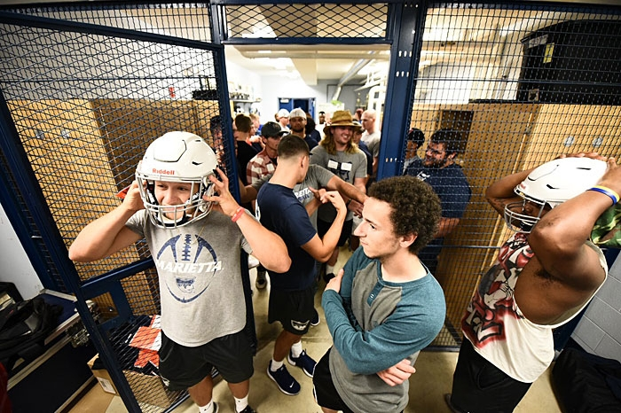 Marietta football players trying on helmets