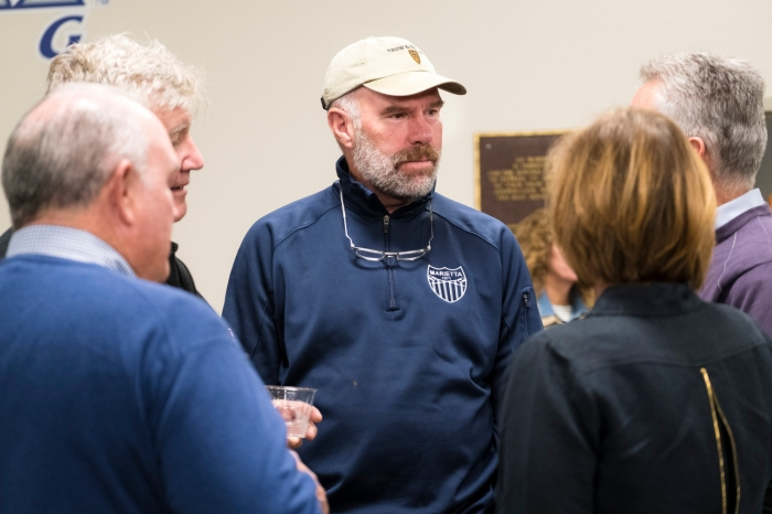 Alumnus Jeff Hugel speaks with other alumni at the boathouse