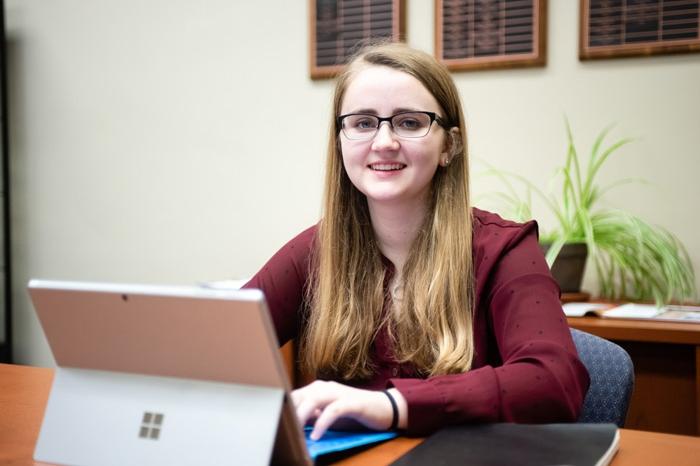 Student Ashley Klopfenstein sitting behind a computer
