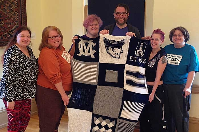 6 people hold blanket with college logos