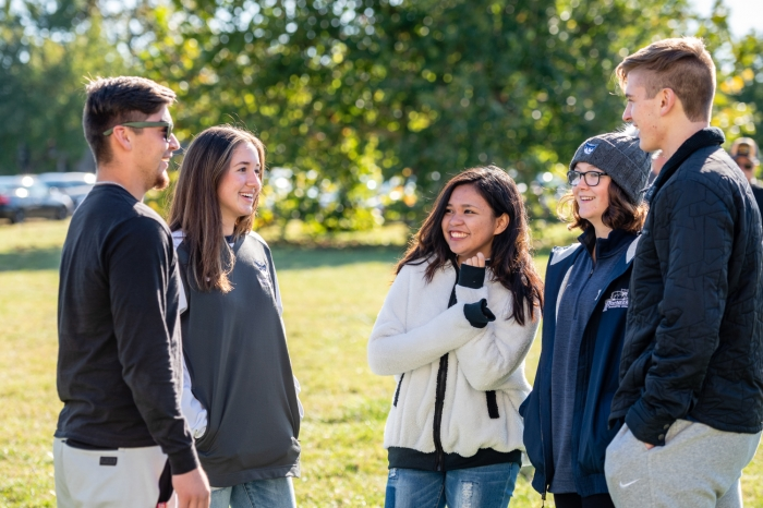 Harrison Scholars - Gabe Brunck, Emi Reindle, Hanna Jamelo, Anna Frost and Artemii Stepanets - chat during halftime of a football game.
