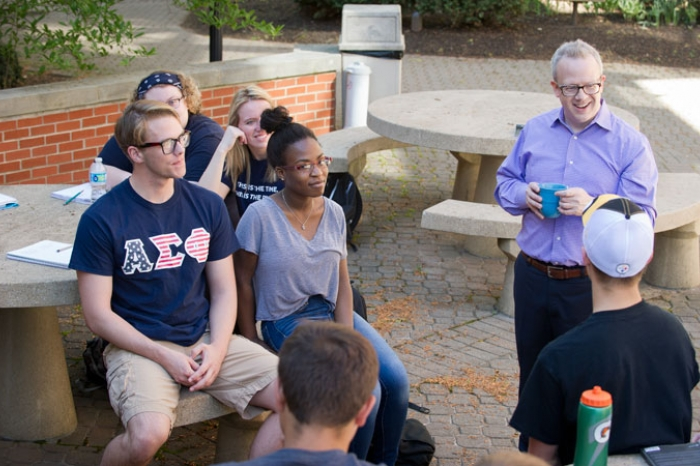 male professor with students outside on campus