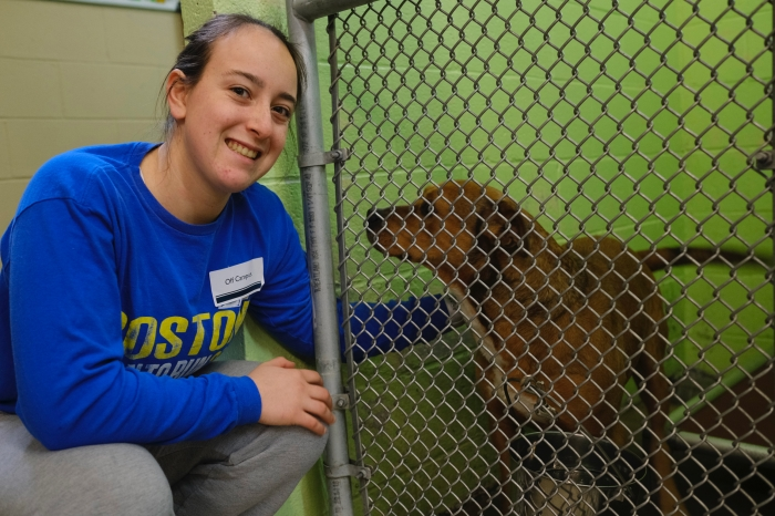 Female student petting a dog at the humane society
