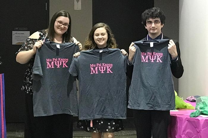 Three students holding up Mu Psi Kappa T-shirts