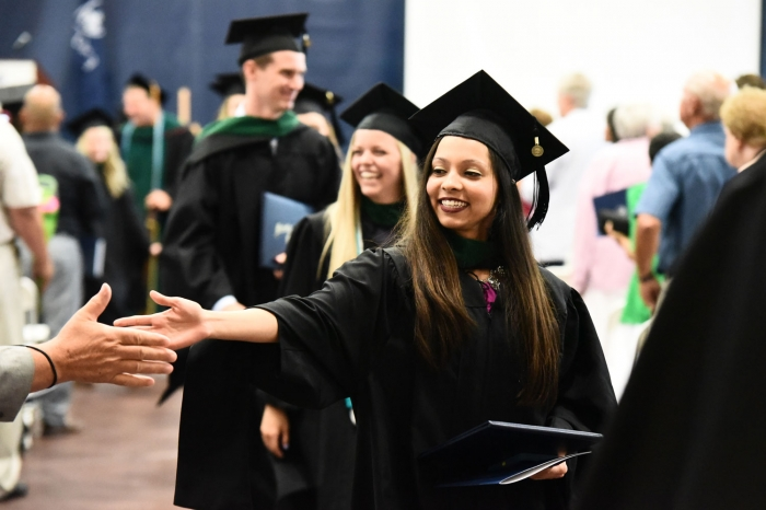 Female student shakes hands after graduating