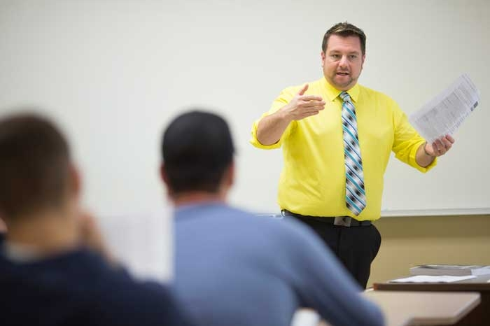 Faculty member Rick Smith teaching in yellow shirt