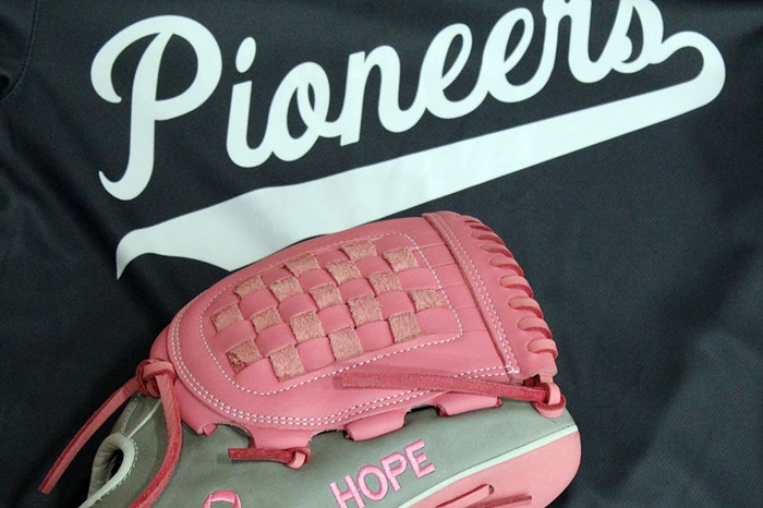 Pink softball glove on top of a softball jersey