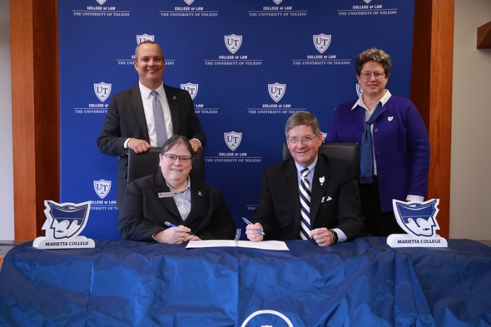 University administrators gathered for a form signing