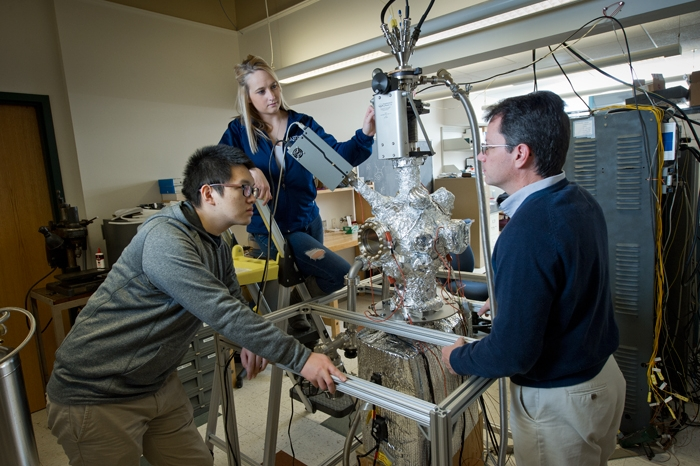 Dr. Dennis Kuhl working with 2 students in physics lab