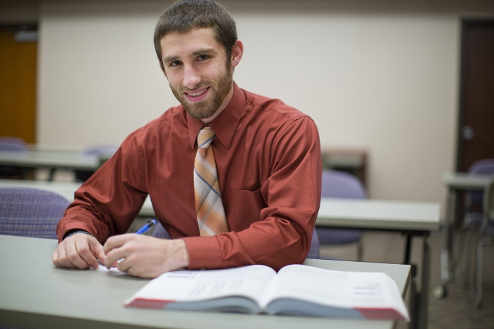 pa student smiles at the camera with book in front of him