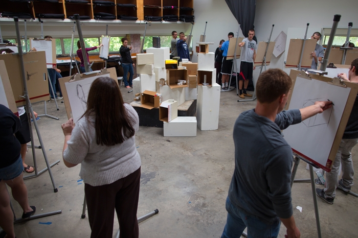 Marietta College students stand and paint in class