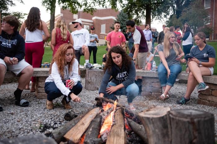 Two female students roasting marshmallows