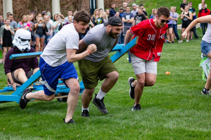 Three male students pulling a chariot during Doo Dah Day