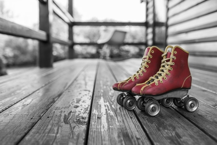 Red roller skates on a porch