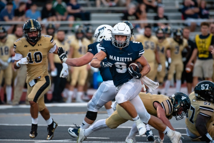 Tanner Clark breaks through the line for a big run in football action