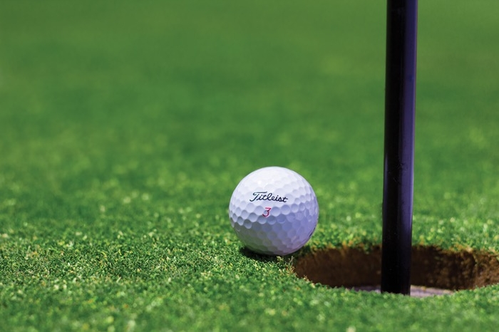 golf ball rolling into hole