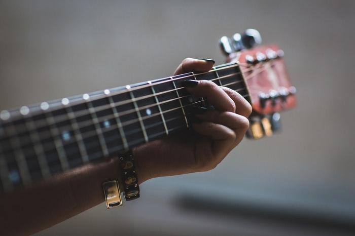 Hand on guitar strings