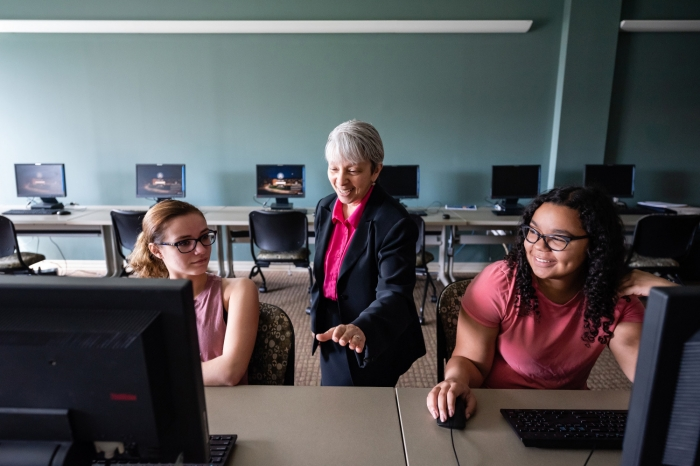 Grace Johnson teaching two students at computers