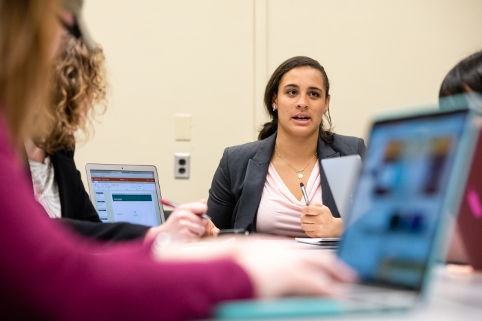 Female student sitting at a table talking with other students on laptops