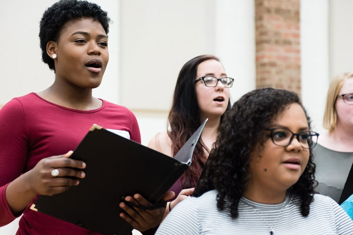 female students singing with the choir