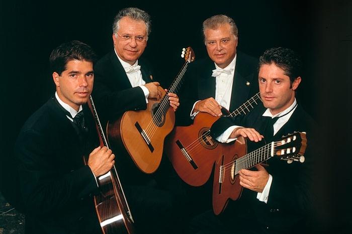 Four men holding guitars