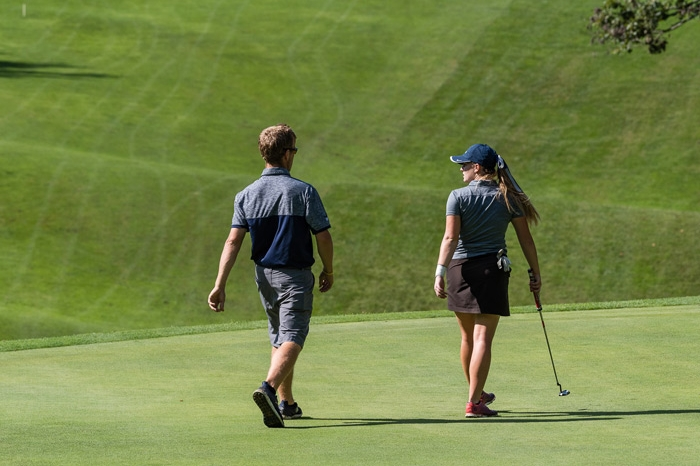 Coach Arison and a women's golfer walking off of the green