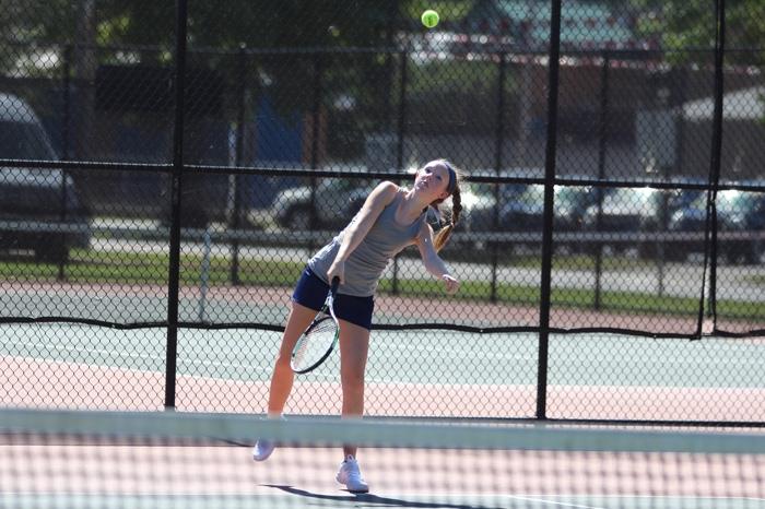 Marietta women's tennis player serving the ball